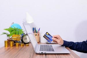 uomo che tiene una carta di credito blu mentre su un computer portatile