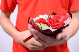 persona che tiene fuori un mazzo di fiori foto