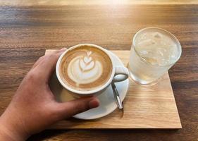caffè caldo in una tazza con schiuma di latte foto