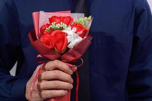 persona in possesso di un bouquet che indossa un abito foto