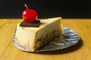 fetta di torta di formaggio con cioccolato e ciliegia sul tavolo di legno foto