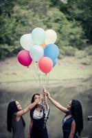 amiche del gruppo felice che tengono palloncini multicolori in un parco foto