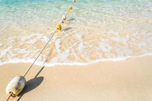 boe sulla corda con le onde dell'oceano sulla spiaggia sabbiosa