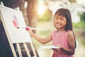 artista della bambina che dipinge un quadro nel parco foto