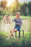 la giovane donna disegna un'immagine nel parco foto