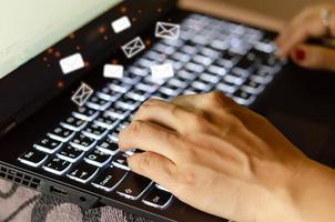 digitando su una tastiera con icone di posta elettronica