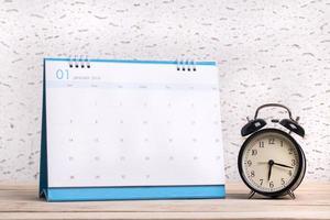 sveglia e calendario su una superficie di legno foto