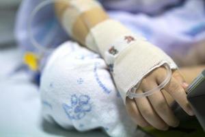 bambino malato in ospedale con iv in braccio