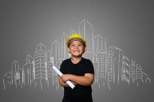 giovane ragazzo che indossa un cappello giallo ingegnere e idee piano casa su una lavagna foto