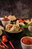 piatto di curry verde con pollo, peperoncino e basilico e pomodoro e lime foto