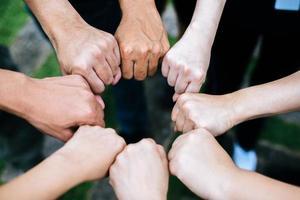 primo piano del gruppo multietnico in piedi con le mani insieme foto