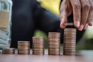mani mettendo insieme pile di monete di denaro in natura foto