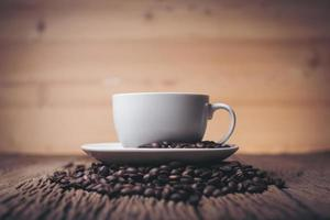 tazza di caffè con chicchi di caffè su un tavolo di legno foto
