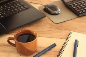 tazza di caffè marrone sulla scrivania foto