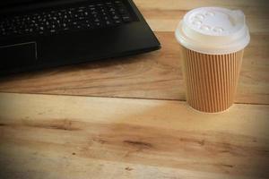 tazza di caffè da asporto sulla scrivania foto