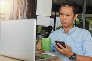 uomo d'affari che tiene telefono e caffè foto