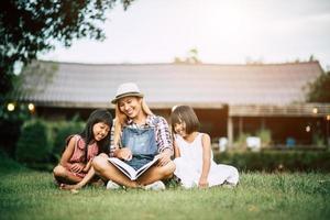 madre che racconta una storia alle sue due figlie piccole nel giardino di casa