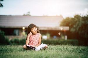 bambina che legge un libro nel giardino di casa sua fuori
