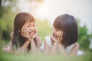 bambine comodamente sdraiate sull'erba e sorridenti foto