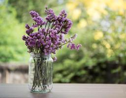 bellissimi fiori in un vaso di vetro sul tavolo di legno foto