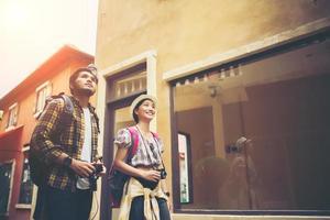 coppia di giovani turisti che camminano in una città urbana godendo insieme delle vacanze foto