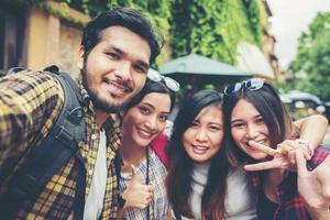 gruppo di amici che prendono un selfie in una strada urbana divertendosi insieme foto