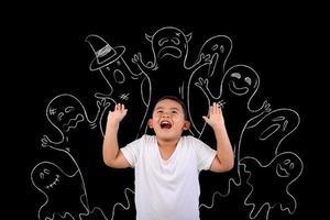giovane ragazzo ha paura dei fantasmi disegnati sulla lavagna foto