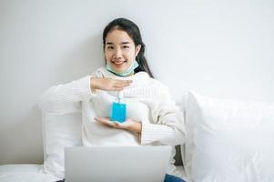 giovane donna sul letto tenendo il gel per il lavaggio delle mani foto