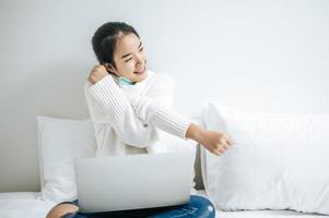 giovane donna che indossa una maschera seduta sul suo letto foto