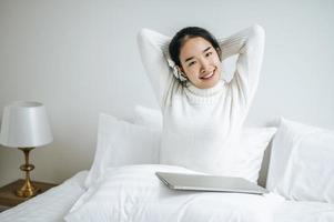 giovane donna che si estende sul letto con il computer portatile foto