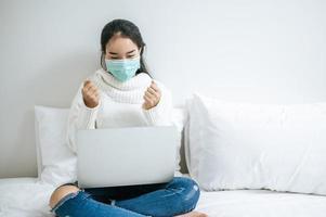 giovane donna che indossa una maschera seduta sul suo letto