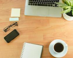disposizione piatta della scrivania con pianta, caffè e telefono foto