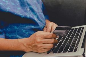 donna che tiene la carta di credito acquisti online
