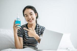 giovane donna utilizzando gel per il lavaggio delle mani foto