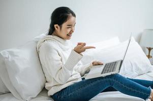 una giovane donna che gioca felicemente sul suo laptop foto