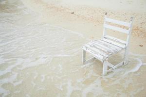 sedia in legno bianco al mare