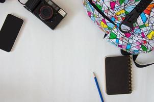 backback, notebook e fotocamera su un tavolo