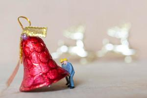 statuette in miniatura di persone che mettono addobbi natalizi