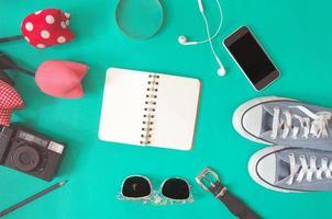 disposizione piatta di notebook, occhiali da sole, fotocamera e converse
