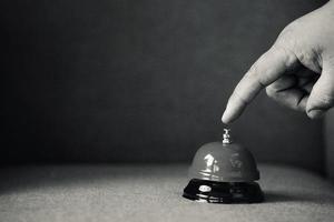 mano che spinge campanello di servizio foto