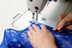 persona che cuce tessuto blu foto