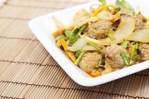 curry di maiale fritto sul piatto bianco foto
