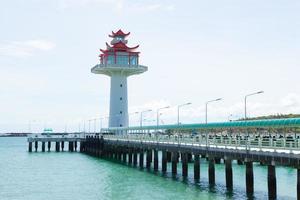 faro e ponte che si protende nel mare foto