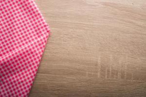 tovagliolo rosso a scacchi su fondo in legno foto