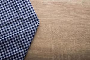 tovagliolo blu a scacchi su uno sfondo di legno foto