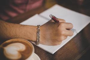 una tazza di caffè sulla barra di legno accanto a un hipster in un bar foto