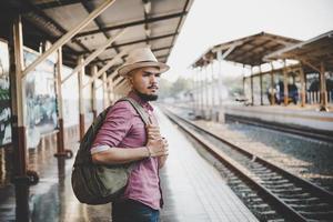 uomo giovane hipster che cammina attraverso la stazione ferroviaria