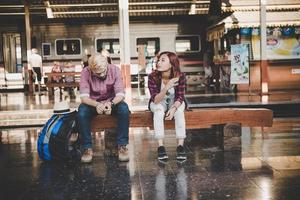 coppia giovane hipster seduto sulla panca in legno alla stazione ferroviaria foto