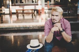 uomo giovane hipster seduto sulla panca in legno con zaino alla stazione ferroviaria