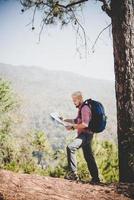 escursionista con mappa e grande zaino da viaggio in viaggio verso la montagna foto